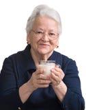拿着玻璃牛奶的健康老妇人 免版税库存照片