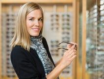拿着玻璃的妇女在眼镜师商店 库存图片