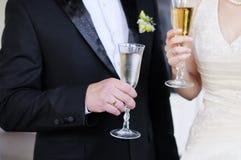 拿着玻璃的新娘和新郎 免版税库存照片