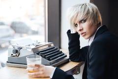 拿着玻璃的美丽的严肃的白肤金发的女孩 免版税图库摄影