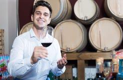 拿着玻璃红葡萄酒和品尝的快乐的顾客 免版税库存图片