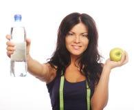 拿着水瓶和绿色苹果的女性健身模型 免版税库存图片