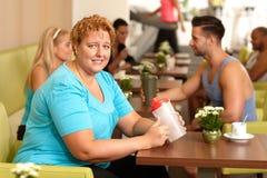 拿着水瓶的健身房的绝望肥胖妇女 库存照片