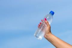 拿着水瓶的妇女手户外 免版税库存图片