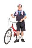 拿着水瓶的成熟骑自行车的人 库存照片