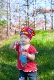 拿着水瓶的明亮的衣裳的小美丽的女孩 免版税图库摄影
