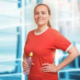 拿着水瓶的年轻微笑的妇女画象在健身房 适应 免版税库存图片