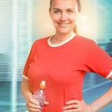 拿着水瓶的年轻微笑的妇女画象在办公室 免版税库存图片