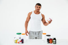 拿着维生素和体育药片的运动员 免版税库存图片