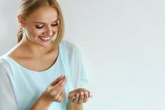 拿着维生素药片的美丽的微笑的妇女手中 健康 免版税库存照片