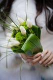 拿着从白色tulipes和金黄讲台的新娘婚礼花束 免版税库存图片
