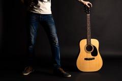 拿着他的与一把声学吉他的吉他弹奏者左手在黑背景 免版税库存照片