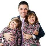 拿着他的两个女儿的衣服的年轻人 图库摄影