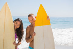 拿着他们的冲浪板的逗人喜爱的年轻夫妇 免版税图库摄影