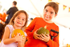 拿着他们的南瓜的两个小女孩在南瓜补丁 库存照片