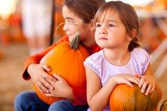 拿着他们的南瓜的逗人喜爱的小女孩在泵浦 免版税库存照片