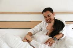 拿着他的在床上的微笑的亚裔新郎新娘 免版税库存照片