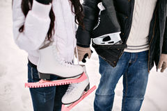 拿着他的在肩膀的年轻爱夫妇冰鞋 男孩节假日位置雪冬天 库存图片
