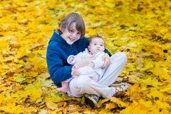 拿着他的在黄色槭树之间的逗人喜爱的兄弟小姐妹 库存图片