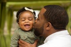 拿着他的女儿的非裔美国人的父亲 免版税库存照片