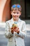 拿着他的宠物小鹅的逗人喜爱的小男孩 免版税库存照片