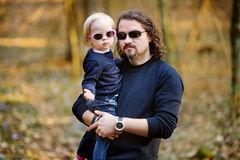 拿着他的小女儿的愉快的年轻父亲 库存照片