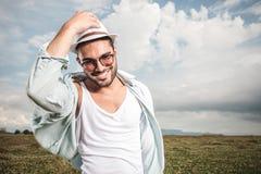 拿着他的帽子的微笑的年轻时尚人 免版税库存照片