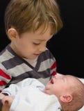 拿着他的弟弟的好奇男孩 免版税库存图片