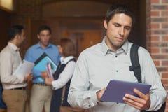 拿着他的片剂的被集中的男性成熟学生站立在走廊 库存图片
