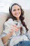 拿着水的舒适长沙发的华美的偶然妇女 免版税库存照片