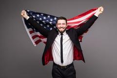 拿着从他的衣服的商人美国旗子与开放嘴 库存照片