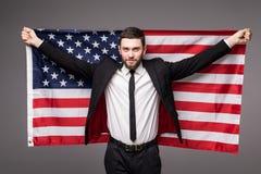 拿着从他的衣服的商人美国旗子与开放嘴 图库摄影
