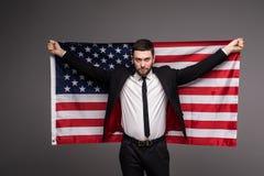 拿着从他的衣服的商人美国旗子与开放嘴 免版税图库摄影
