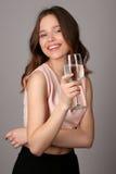 拿着水的酒杯夫人 关闭 灰色背景 库存图片