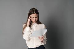 拿着他的头读书文件的女实业家 在灰色背景 女实业家纵向 免版税库存照片