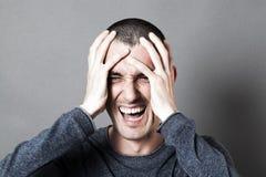 拿着他的头的恼怒的年轻人,尖叫他的烧坏 免版税库存照片