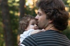 拿着他的他的胳膊的爸爸小蓝眼睛的女儿步行的在公园 夏日,家庭自然步行,晴朗 免版税库存图片