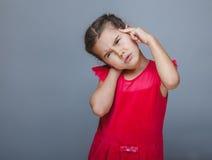 拿着他的头的青少年的女孩儿童头疼偏头痛 免版税图库摄影