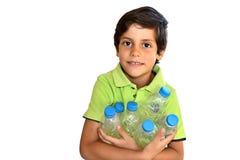 拿着紧的plastc瓶的男孩 免版税库存图片