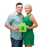 拿着绿皮书房子的微笑的夫妇 免版税库存图片