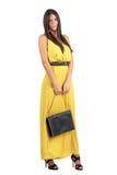 拿着黑皮包的黄色连衫裤的肉欲的可爱的妇女 免版税库存照片
