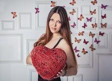 拿着紫皮柳树的心脏的美丽的妇女 库存图片