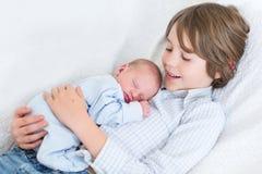 拿着他睡觉的新出生的小兄弟的愉快的笑的男孩 库存照片
