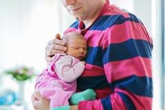 拿着他睡觉的新出生的小女儿的愉快的骄傲的年轻父亲 库存图片