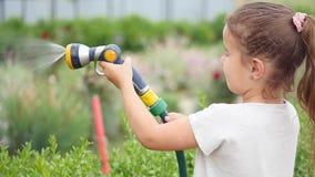 拿着水水管和震动它的逗人喜爱的小女孩作为她浇灌草坪 股票视频