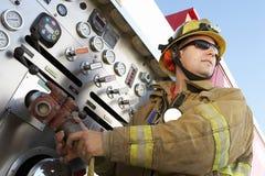 拿着水管的消防队员 免版税库存照片