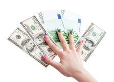拿着100美元和欧洲钞票的妇女的手 免版税库存照片