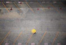 拿着黄色伞和单独走通过汽车停车场背景的女商人鸟瞰图 库存照片