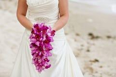拿着紫色兰花花婚礼花束的新娘 免版税库存照片