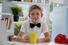 拿着黄色咖啡杯的微笑的商人在书桌 图库摄影